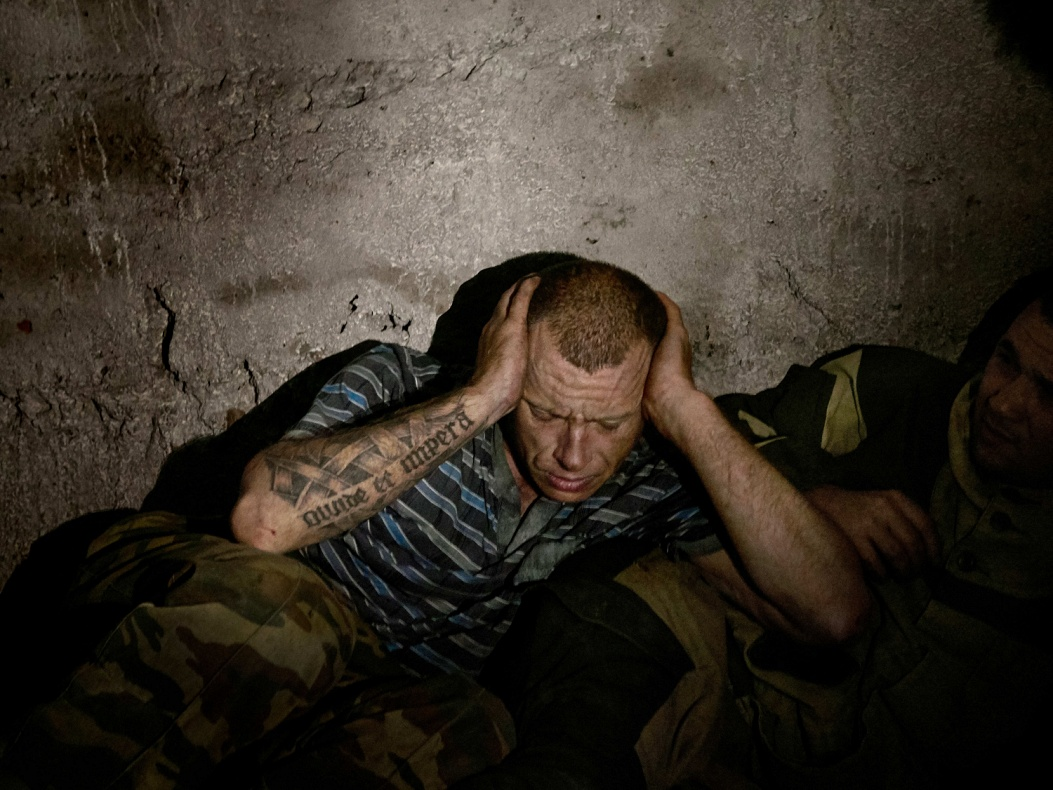 """Ukraine; Donbass region; Spartak; 2016  Exhausted soldier in a shelter. Near the frontline in the area of Spartak the Ukrainian division attacks with overnight heavy shellings. """"Unpredictable spikes in the armed hostilities further exacerbated the situation of general insecurity"""" (UNHR report)."""